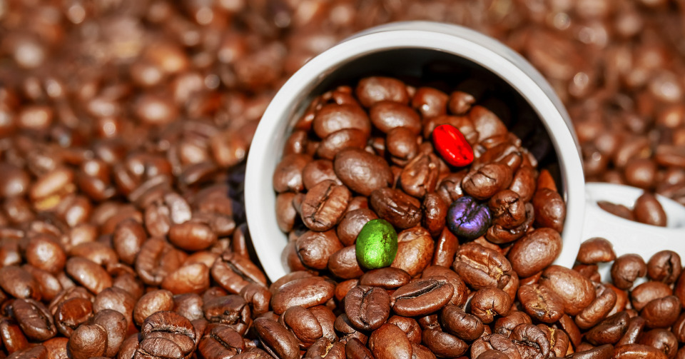 A lot of coffee beans with a partially filled cup laying on it. 3 beans in a cup have different color
